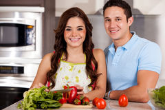 Cooking dinner on a date. Beautiful young brunette and her date making a salad for dinner Royalty Free Stock Photos