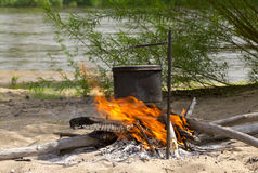 Cooking dinner on fire. Cooking dinner in a campaign on fire Stock Photography
