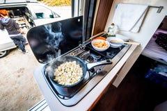 Cooking dinner or lunch in campervan, motorhome or RV. Preparing chicken in a pan in camper van when traveling with RV, motor home caravan or motorvan. Vanlife stock images