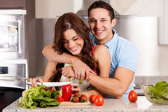 Cooking dinner for my date. Gorgeous young women making a salad with her date for dinner Royalty Free Stock Image