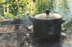 Cooking dinner in old camping kettle on picnic. Closeup. Royalty Free Stock Images