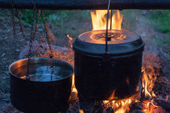 Cooking dinner in sooty metal pots on bonfire at camping.  Stock Images
