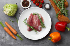 Cooking duck breast. Raw duck breast, fresh vegetables, herbs and spices on gray stone background, top view Royalty Free Stock Image