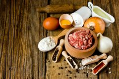 Cooking dumplings: minced meat, onion, salt, pepper, flour, egg,. Oil on old wooden table, rustic style, selective focus Royalty Free Stock Photo
