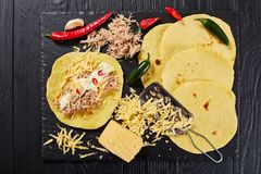 Cooking enchiladas of corn tortillas, cheese, meat. Homemade corn tortillas layered with shredded meat, sauce, grated cheese and spices on black stone board, on Royalty Free Stock Photography
