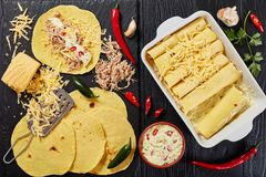 Corn tortillas layered with shredded meat. Cooking enchiladas - homemade corn tortillas layered with shredded meat, sauce, grated cheese and spices in baking Stock Photo