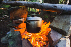 Cooking on fire in camp in mountain forest Stock Photos