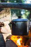 Cooking on fire in camp in mountain forest Stock Photography
