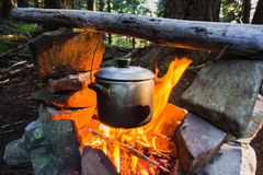 Cooking on fire in camp in mountain forest Royalty Free Stock Images