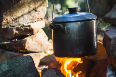 Cooking on fire in camp in mountain forest Stock Photo