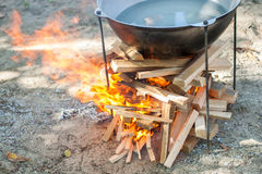 Cooking on a fire. Food in a cauldron on a fire. Food outdoors. Cooking outdoors. Cooking in nature on the cauldron. Water in copper on fire Stock Photography