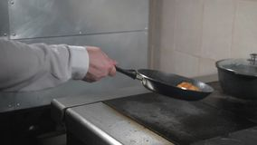 Cooking with fire in frying pan. chicken breast. Professional chef in a commercial kitchen cooking. Man frying food in. Pan on hob in kitchen. slow motion stock footage