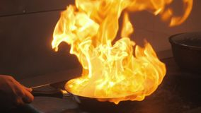 Cooking with fire in frying pan. chicken breast. Professional chef in a commercial kitchen cooking. Man frying food in. Pan on hob in kitchen. slow motion stock video footage