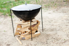 Cooking on a fire. Ignition of a fire. Food in a cauldron on a fire. Food outdoors. Cooking outdoors. Cooking in nature on the cauldron Stock Photos