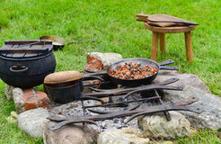 Cooking on fire outdoors Stock Images