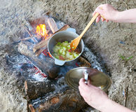Cooking on fire at picnic, food prepared in pot on wood, potatoes and tomatoes, healthy vegetarian food, woman hands with spoon Royalty Free Stock Image
