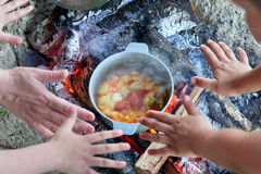 Cooking on fire at picnic, hands around food prepared in kettle on wood, potatoes and tomatoes, healthy vegetarian food Stock Photography