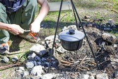 Cooking on a fire at spring. Close view of caldron over the campfire. Man is making a fire, body parts. Pot over the fire in the forest. Cooking on a fire royalty free stock images