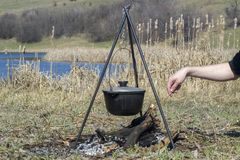Cooking on a fire at spring. Close view of caldron over the campfire. Pot over the fire in the forest. Cooking on a fire. Spring camping concept. Man`s hand puts royalty free stock photo