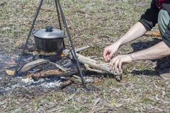 Cooking on a fire at spring. Close view of caldron over the campfire. Pot over the fire in the forest. Cooking on a fire. Spring camping concept. Man`s hand puts stock images