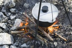 Cooking on a fire at spring. Close view of caldron over the campfire. Pot over the fire in the forest. Cooking on a fire. Spring camping concept. Opening of the stock image