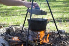 Cooking on a fire at spring. Close view of caldron over the campfire. Pot over the fire in the forest. Cooking on a fire. Spring camping concept. Opening of the royalty free stock images
