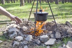 Cooking on a fire at spring. Close view of caldron over the campfire. Pot over the fire in the forest. Cooking on a fire. Spring camping concept. Opening of the stock photography