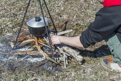 Cooking on a fire at spring. Close view of caldron over the campfire. Pot over the fire in the forest. Cooking on a fire. Spring camping concept. Man`s hand puts royalty free stock photography
