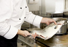 Cooking fish. Men cooking fish in gourmet cuisine Royalty Free Stock Photo