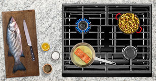 Cooking fish on gas stove Stock Photography