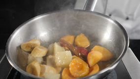 Cooking flambe dessert with fruit: banana, apricots and peach. Chef stirring and tossing frying pan with caramelized. Fruits. Roast ingredients for delicious stock video