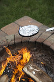 Cooking a foil covered pan of popcorn on fire pit Stock Photo