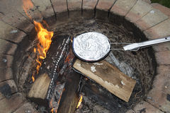 Cooking a foil covered pan of popcorn on fire pit Royalty Free Stock Images