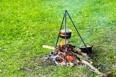 Bowler on a tripod over a fire, cooking food in a field tent camp Royalty Free Stock Photo