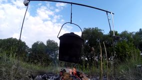 Cooking food on the campfire on river bank 3 stock footage