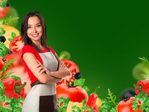 Cooking and food concept - smiling female chef, cook or baker with fork showing crossed arms sign over falling vegetables on green Stock Photos