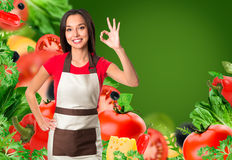 Cooking and food concept - smiling female chef, cook or baker with fork showing ok sign over falling vegetables on green Royalty Free Stock Images