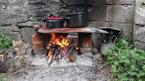 Cooking food on the fireplace. In field conditions stock video