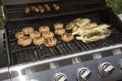 Cooking food on a gas barbecue. Food cooking on a gas barbecue. Sausages,turkey burgers and corn Royalty Free Stock Photos
