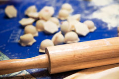 Cooking food. Homemade pelmeni covered with flour on a wooden table with rolling pin Royalty Free Stock Photos