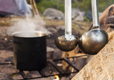 Cooking food in the nature. Big pot on fire and ladle in forest. Royalty Free Stock Photography