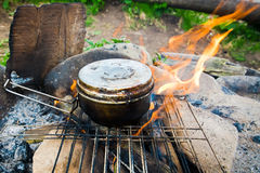 Cooking food in old tourist pot at fire place Stock Photo