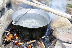 Cooking food with old tourist pot at outdoor fire place. Summer. Trekking activity Royalty Free Stock Image