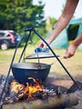 Cooking food over campfire in hike Stock Photos