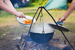 Cooking food over campfire in hike Royalty Free Stock Photography