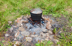 Cooking food over an open fire at the campsite in summer Royalty Free Stock Photos