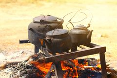 Cooking food in a rustic old kettle on bonfire in the forest. royalty free stock image