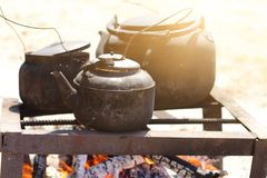 Cooking food in a rustic old kettle on bonfire in the forest. stock photo