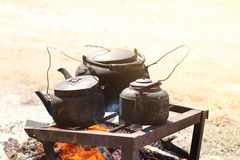 Cooking food in a rustic old kettle on bonfire in the forest. royalty free stock photos