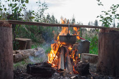 Cooking food at the stake. Cooking food in a pot in the fire royalty free stock photos
